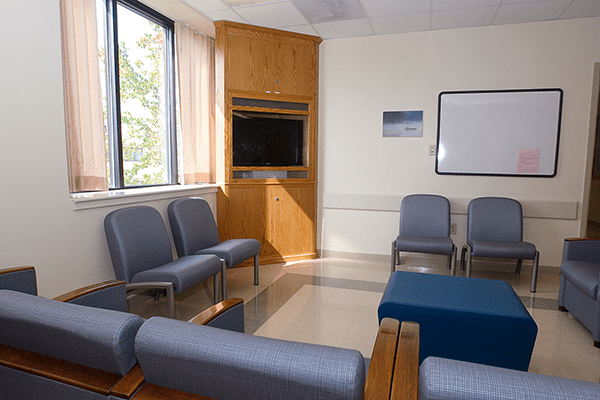 The bright and sunny community room includes comfortable chairs and a television.
